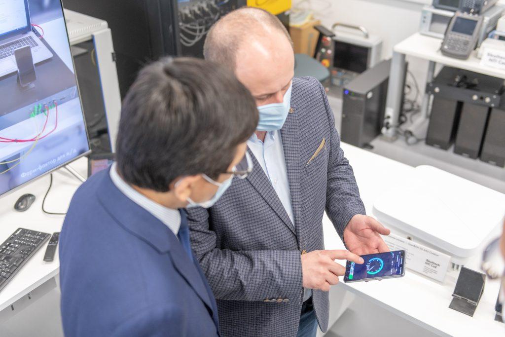 Дмитрий Лаконцев демонстрирует Асхату Аймагамбетову скорость передачи данных у подключенных к Пилотной зоне 5G смартфонов (1,4 гигабита в секунду).